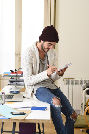 informal: young trendy businessman in cool hipster beanie and informal look writing on pad working happy at modern home office as creative designer in freelance business success concept Stock Photo