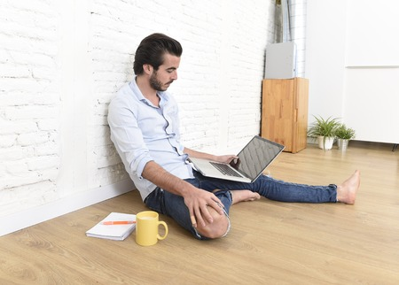 unfurnished: young attractive latin man in hipster and modern casual style look sitting on unfurnished living room home floor working on laptop computer drinking coffee in internet concept