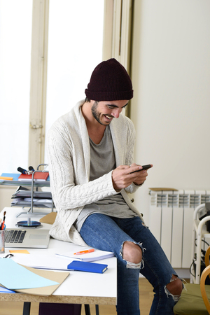 informal: young trendy businessman in beanie and cool hipster informal look sitting on office desk using internet on mobile phone samiling happy and confident  in freelance business success concept