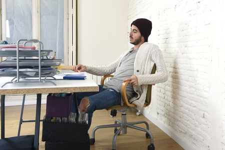 beanie: young trendy businessman in cool hipster beanie look working with laptop computer  analyzing project working in at modern home office as creative designer in freelance business concept Stock Photo