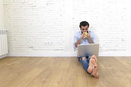 unfurnished: young attractive latin man in hispter and modern casual style look sitting on unfurnished living room home floor working on laptop computer drinking coffee in internet communication concept