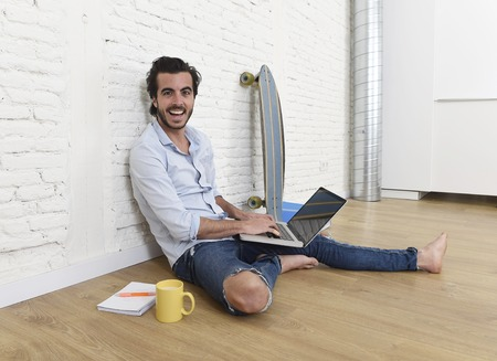 unfurnished: young attractive latin man in hipster and modern casual style look sitting happy on unfurnished living room home floor working on laptop computer drinking coffee in internet concept