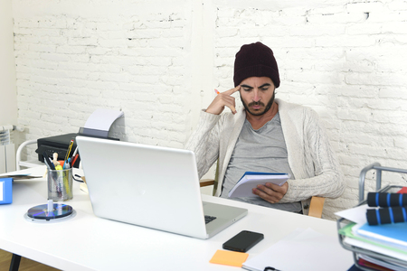 young trendy businessman in cool hipster beanie look thinking and writing on pad working in at modern home office with computer laptop as creative designer in freelance business concept