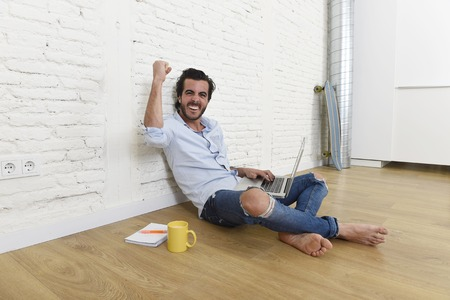 unfurnished: young attractive latin man in hipster and modern casual style look sitting happy on unfurnished living room home floor working on laptop computer gesturing excited on victory and success