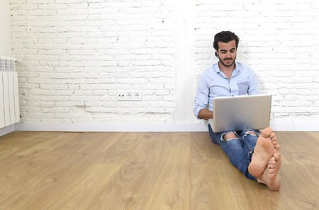 unfurnished: young attractive Latin man in hipster and modern casual style look sitting on unfurnished living room home floor working on laptop computer smiling happy in internet communication concept