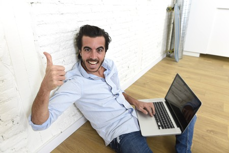 unfurnished: young attractive latin man in hipster and modern casual style look sitting happy on unfurnished living room home floor working on laptop computer gesturing excited giving thumb up Stock Photo