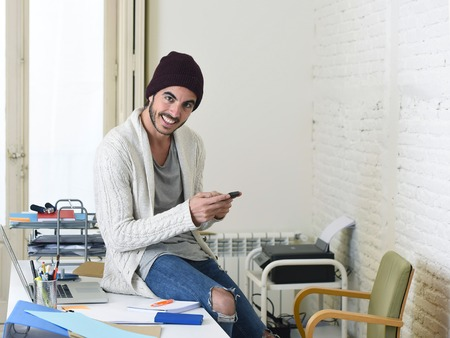 beanie: young trendy businessman in beanie and cool hipster informal look sitting on office desk using internet on mobile phone samiling happy and confident  in freelance business success concept