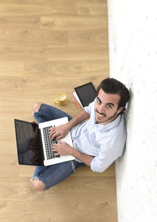 unfurnished: young attractive latin man in hipster and modern casual style look sitting happy on unfurnished living room home floor working on laptop computer in internet concept view from above Stock Photo