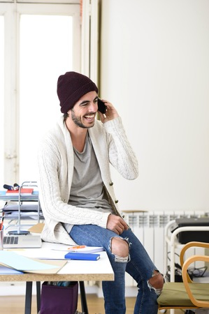 informal: young trendy businessman in beanie and cool hipster informal look sitting on office desk talking excited on mobile phone smiling happy and confident  in freelance business success concept Stock Photo