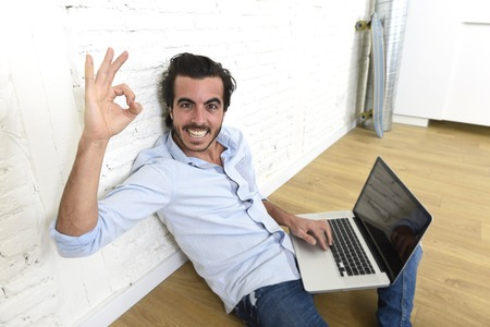unfurnished: young attractive latin man in hipster and modern casual style look sitting happy on unfurnished living room home floor working on laptop computer gesturing excited giving okay hand sign