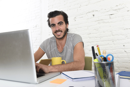 informal clothing: young modern hipster style student or businessman working with laptop computer at home office smiling happy and satisfied in creative freelance business success concept