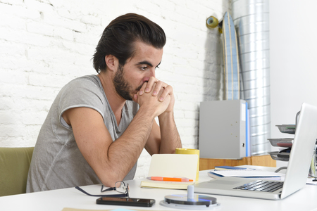 informal: young student preparing exam thinking or informal hipster style businessman working with laptop computer at home office looking thoughtful in new business and lifestyle concept