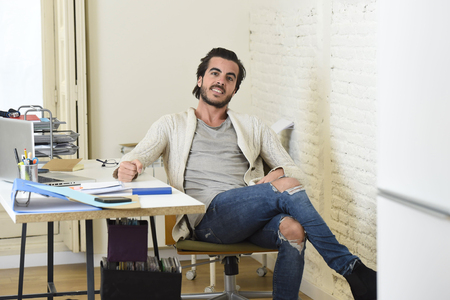 happy handsome student or hipster trendy style businessman wearing battered denim jeans posing corporate on desk at modern home office in creative freelancer business success concept