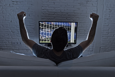 back screen: back view of young man home alone watching soccer or football game in television enjoying and celebrating goal and victory gesturing with fist sitting on the sofa happy and excited Stock Photo