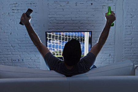 back screen: young man home alone watching soccer or football game in television enjoying and celebrating goal and victory holding beer bottle and TV controller gesturing on the sofa happy and excited