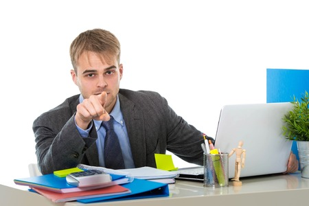 businessman working at his computer: young attractive businessman working busy with laptop computer at office pointing with his finger in business project success concept isolated on white background