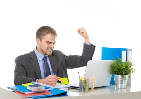 euphoria: corporate portrait of young attractive businessman gesturing and celebrating business success excited raising his fist in victory and euphoria concept isolated on white background