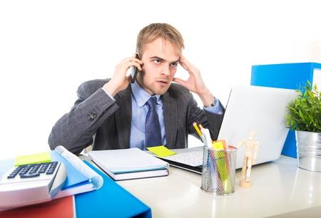 kaukasischen junge attraktive Geschäftsmann besorgt und müde reden über Handy auf Laptop-Computer Schreibtisch sitzen in Stress arbeiten lastet und frustriert auf weißem Hintergrund