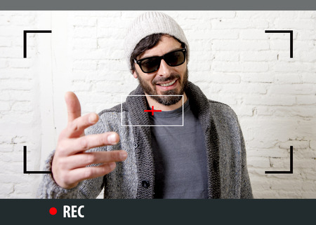young attractive vlog hipster and trendy style looking man smiling happy  talking to camera posing cool with attitude dressing informal in selfie and internet video blogger recording Stockfoto
