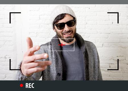 jonge aantrekkelijke vlog hipster en trendy stijl uitziende man lacht graag in gesprek met de camera poseren koel met attitude dressing informele in selfie en internet video-opname blogger