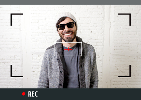 informal: young attractive vlog hipster and trendy style looking man smiling happy  talking to camera posing cool with attitude dressing informal in selfie and internet video blogger recording Stock Photo