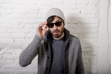 informal: young attractive hipster and trendy style looking man posing cool with attitude dressing informal wearing casual beanie beard and sunglasses in male fashion concept