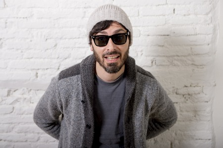 beanie: young attractive hipster and trendy style looking man posing cool with attitude dressing informal wearing casual beanie beard and sunglasses in male fashion concept