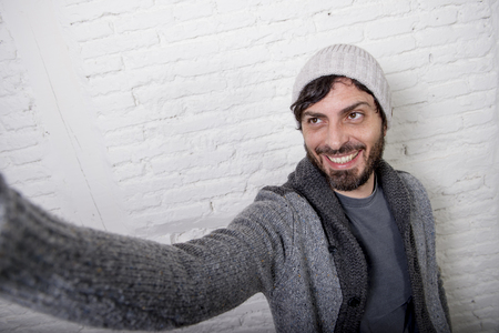 beanie: young attractive man in casual clothes beanie hipster style holding off screen mobile phone shooting self portrait photo selfie or recording video in internet blog and blogger concept