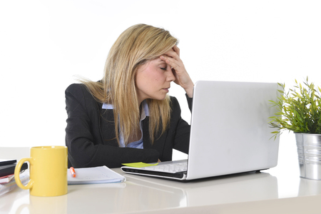 young beautiful business woman suffering stress working at office computer desk feeling tired and desperate looking overworked covering face with hands overwhelmed and frustrated