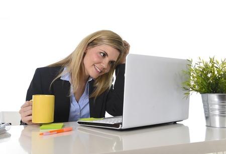 mujeres trabajando: retrato de joven mujer de negocios corporativa rubia caucásica feliz trabajando en equipo portátil en el escritorio de oficina moderna sonriente el consumo de café confianza en el éxito concepto de mujer ejecutiva