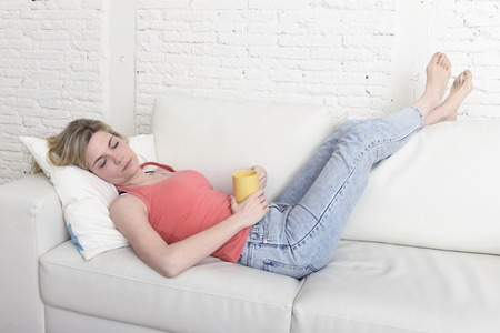 young attractive blond hair woman holding cup of coffee lying on sofa couch at home living room taking a nap and sleeping relaxed in lifestyle concept