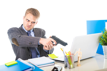 long hours: young overworked and overwhelmed businessman in upset face expression holding gun pointing to computer suffering stress in business long hours working concept Stock Photo