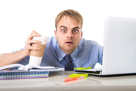 junkie: coffee junkie businessman holding take away cup looking with crazy eyes and funny face expression overworked working at office computer desk in caffeine addiction concept