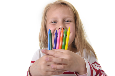 crayons: 6 or 7 years old beautiful little girl holding multicolor crayons set in art school children education concept isolated on white background Stock Photo
