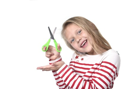 8 years old: sweet beautiful female child 6 to 8 years old with cute blonde hair and blue eyes holding cutting scissors isolated on white background in education and primary or junior school supplies concept
