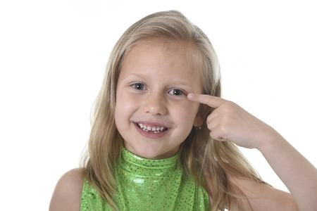 6 7 years: 6 or 7 years old little girl with blond hair and blue eyes smiling happy posing isolated on white background pointing eye in language lesson for child education and body parts school chart serie