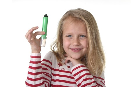 8 years old: sweet beautiful female child 6 to 8 years old with blonde hair and blue eyes holding drawing - writing marker isolated on white background in education and primary or junior school supplies concept Stock Photo