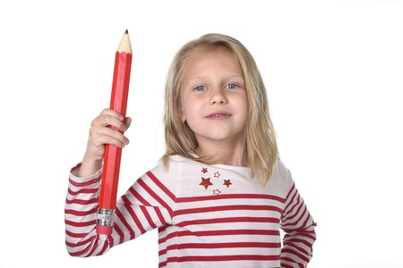 8 years old: sweet beautiful female child 6 to 8 years old with cute blonde hair and blue eyes holding huge pen isolated on white background in education and primary or junior school supplies concept