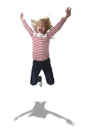 8 years old: sweet beautiful 6 to 8 years old female child with blond hair jumping happy and crazy rising arms in body language education concept isolated on white background