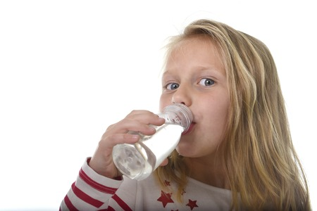 7 years old: cute sweet little girl with blue eyes and blond hair 6 or 7 years old holding bottle of water drinking isolated on white background