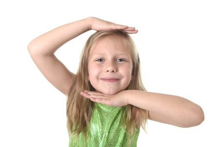 7 years old: 6 or 7 years old little girl with blond hair and blue eyes smiling happy posing isolated on white background showing head in language lesson for child education and body parts school words chart serie Stock Photo