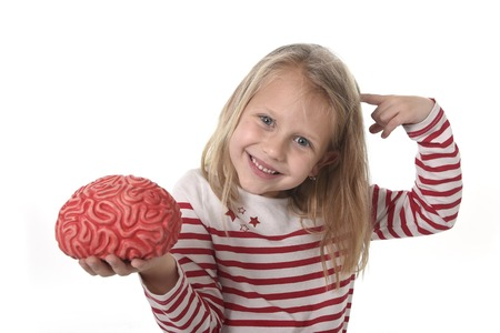 8 years old: young beautiful girl 6 to 8 years old playing with rubber brain having fun isolated on white background in wisdom and learning science at school and  education concept