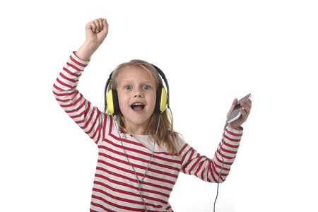 7 years old: sweet little girl 7 years old with blonde hair and blue eyes listening to music with headphones and mobile phone singing and dancing happy isolated on white background Stock Photo