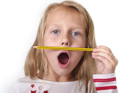 niños rubios: hermosa dulce niña de 6 a 8 años de edad con el pelo rubio y los ojos azules lindo que sostiene un lápiz aislado sobre fondo blanco en educación y suministros de la escuela primaria o secundaria concepto Foto de archivo