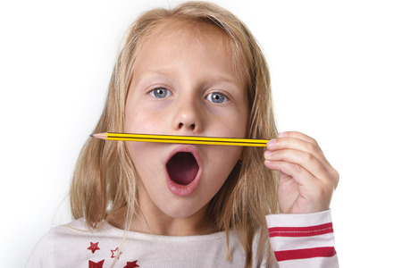 8 years old: sweet beautiful female child 6 to 8 years old with cute blonde hair and blue eyes holding pencil isolated on white background in education and primary or junior school supplies concept