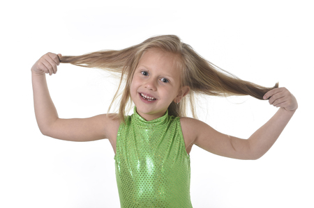 6 or 7 years old little girl with blue eyes smiling happy posing isolated on white background pulling her blond hair in language lesson for child education and body parts school chart serie Banco de Imagens