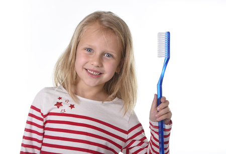 huge: sweet beautiful 6 to 8 years old female child with blond hair and big blue eyes holding huge toothbrush smiling happy in dental care and healthy lifestyle education concept isolated white background Stock Photo
