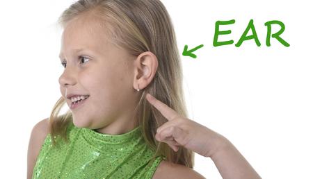 blonde yeux bleus: 6 ou 7 ans petite fille aux cheveux blonds et yeux bleus souriant heureux posant isolé sur fond blanc oreille pointant dans l'apprentissage de la langue anglaise l'éducation scolaire carte des parties du corps ensemble