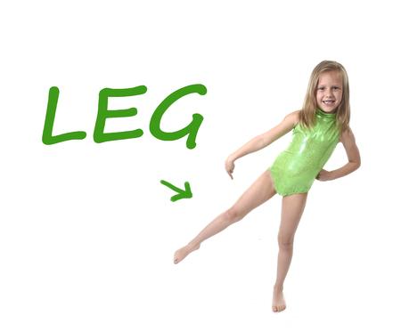 niña de 6 o 7 años de edad con el pelo rubio y los ojos azules que sonríe feliz posando aisladas sobre fondo blanco señalando la pierna en el aprendizaje de Inglés idioma ajustado educación tarjeta de partes del cuerpo de la escuela Foto de archivo