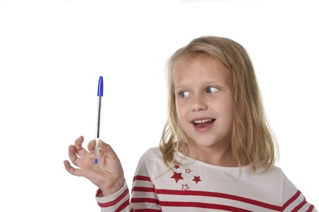 8 years old: sweet beautiful female child 6 to 8 years old with cute blonde hair and blue eyes holding ball pen isolated on white background in education and primary or junior school supplies concept